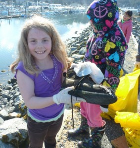 A student volunteer finds an old boot during the harbor clean-up