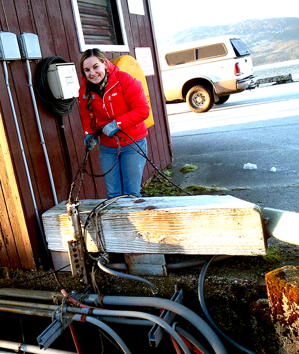 Megan Roberts retrieves the conductivity sensor at the Cordova tide station to inspect it for fouling.